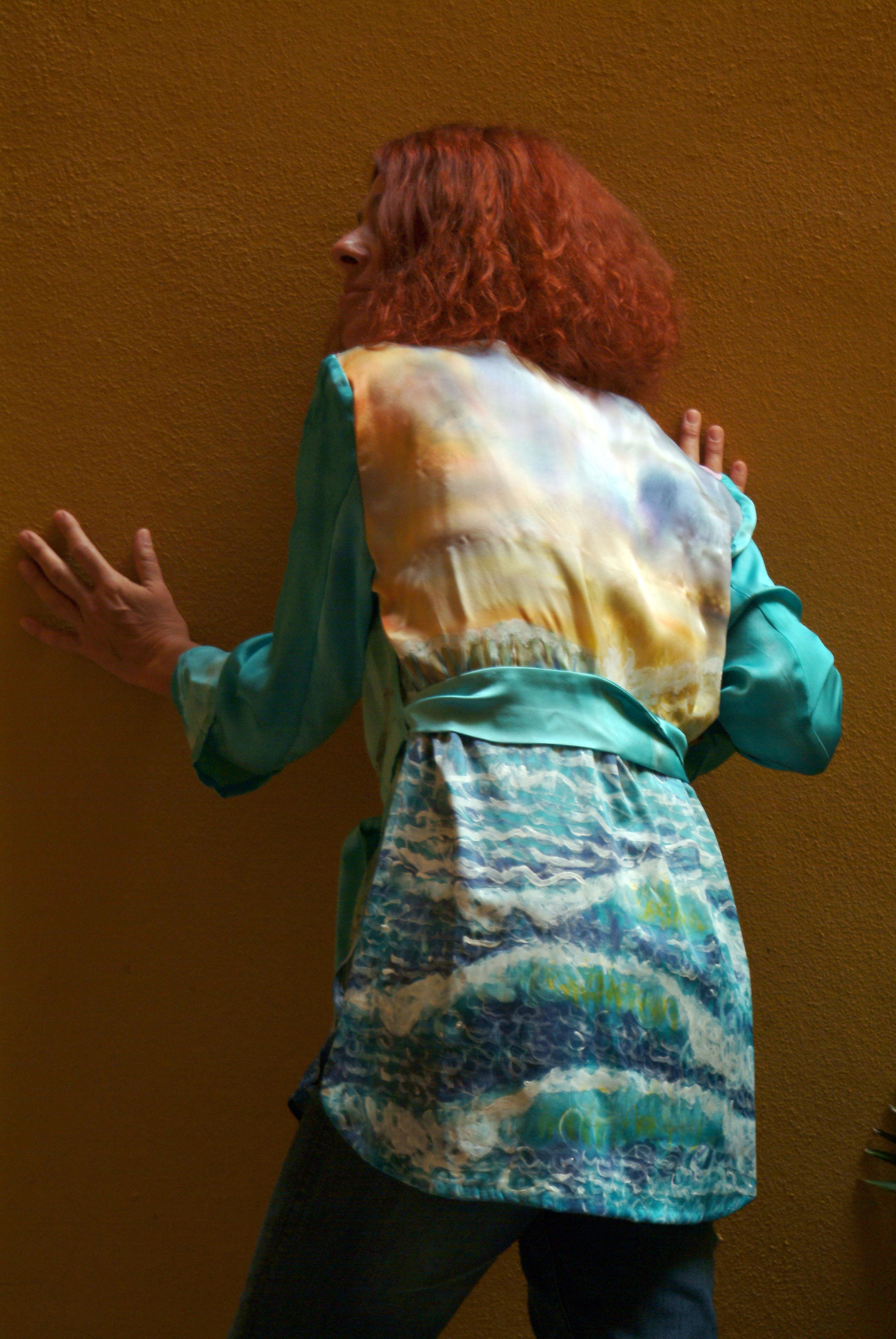 Palmira de espaldas con el blusón pintado con el mar en movimiento, crepe satén. Fotografía: Vicente Alamán Picazo..