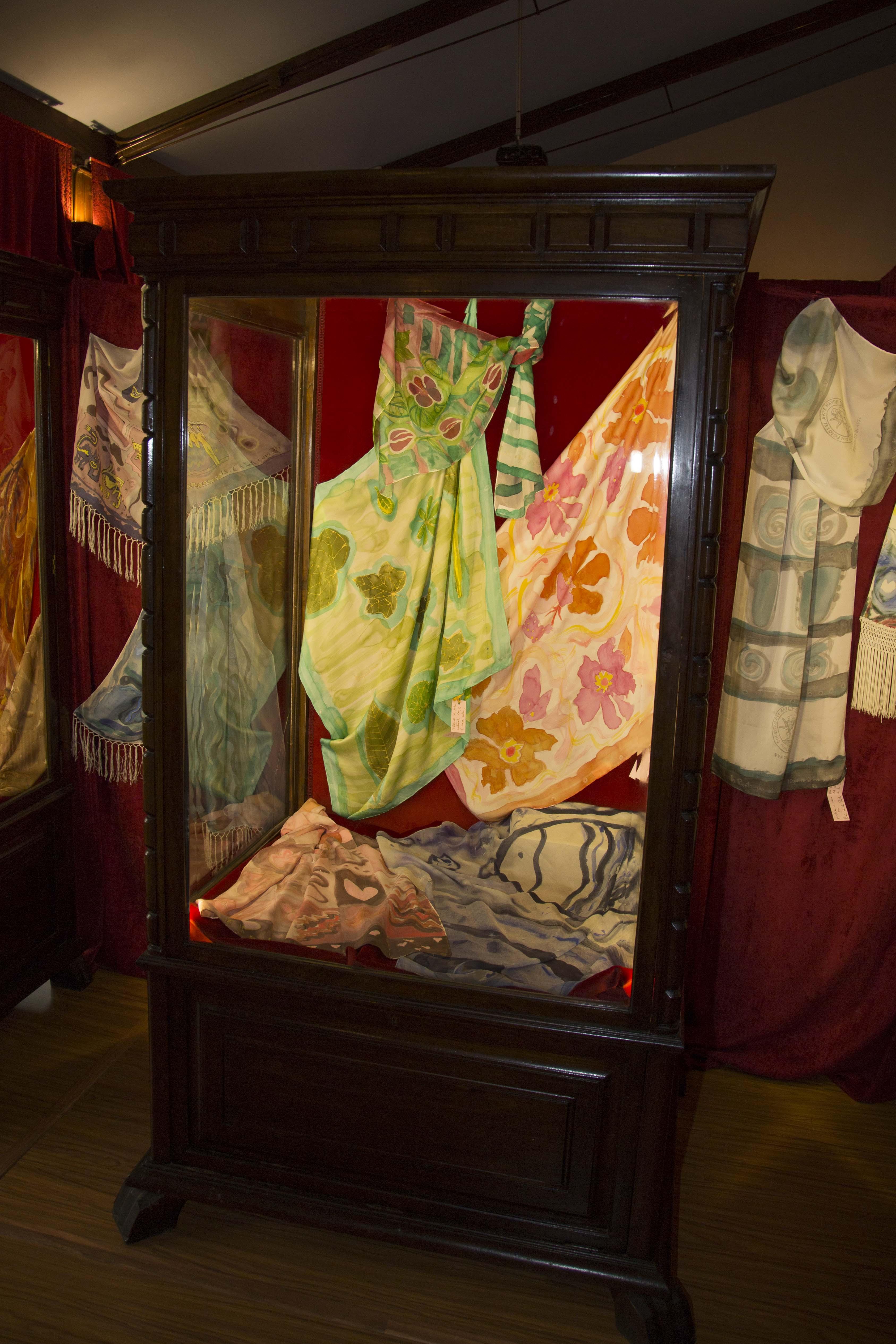 Vitrinas con pañuelos a flores y hojas verdes  en la Exposición Colegio del arte mayor de la seda de Valencia. Fotografía: Baúl de Fotos.
