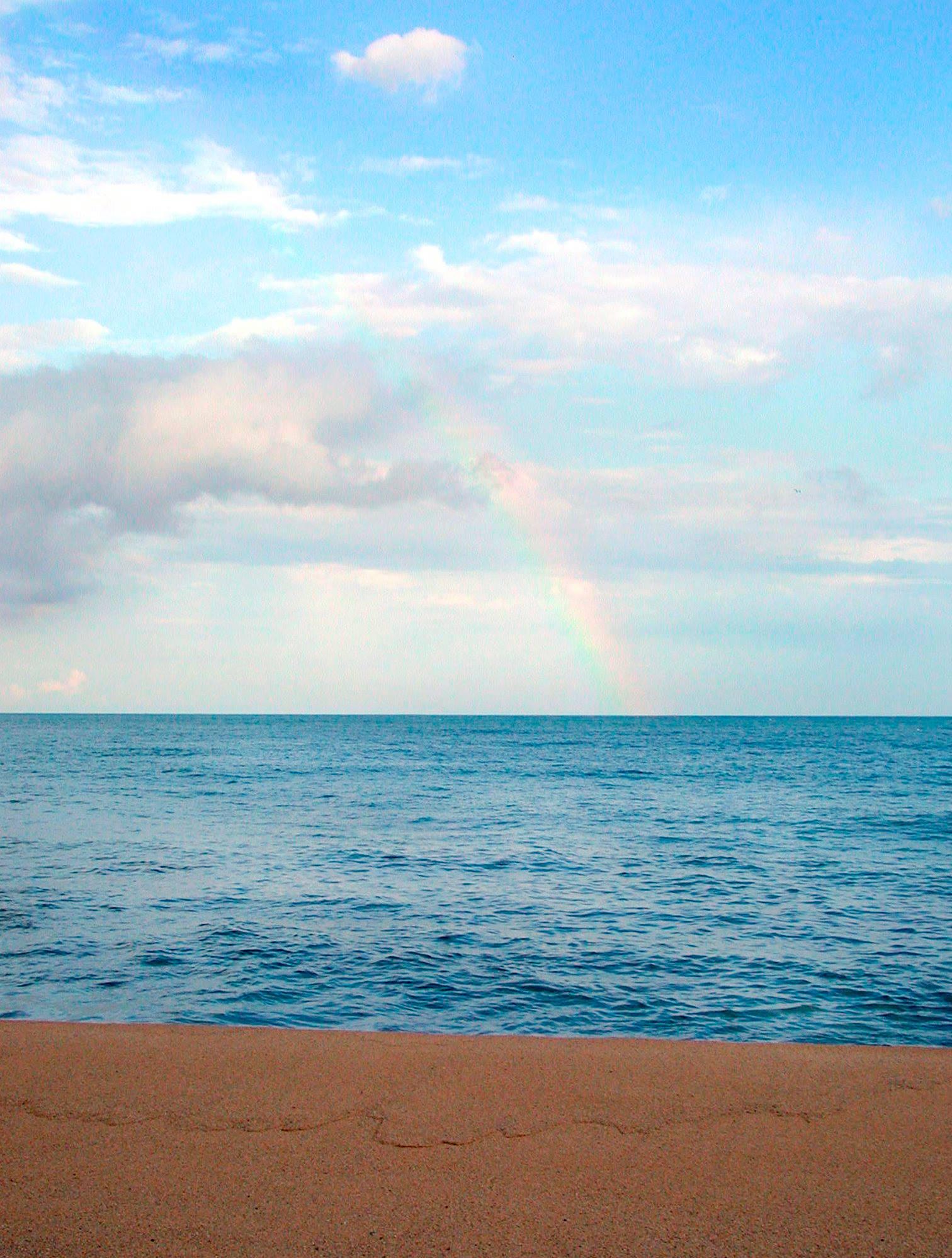 Fotografia de Cote Cabrera sobre el mar  con arcociris.